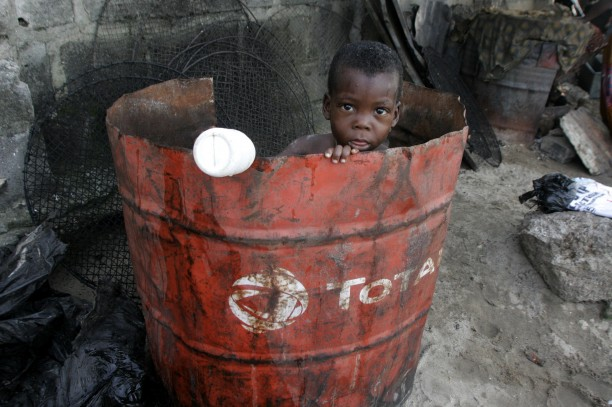 Doyin Ajala plays inside an oil drum at the waterfront in Lagos, Nigeria. A new report measuring one form of corruption shows that Nigeria, an oil rich nation, lost at least $12.89 billion in illicit financial outflows in 2011.