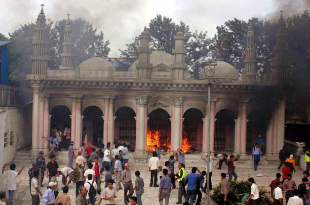 Protesters attack a burning mosque in Katmandu, Nepal in 2004, to protest the killing of 12 Nepalese hostages by Iraqi militants.