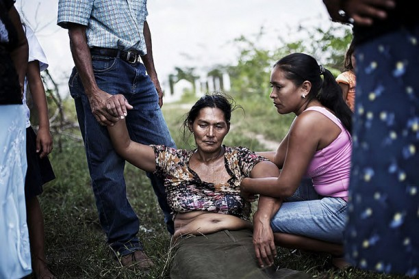 The mother of a campesino killed by security forces acting on behalf of a landowner collapses at her son's funeral.