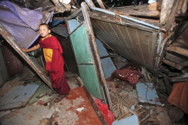 A young Buddhist monk stands near the rubble at Enchey Monastery in Gangtok, India, after the earthquake.