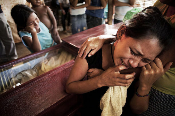 Family members weep over the body of a peasant killed in the Bajo Aguán community of Panamá in Honduras.