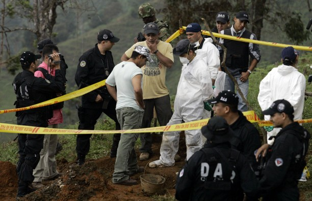 "Colombian police look at the human remains found in a mass grave of at least 20 bodies in El Arenillo, northeast of Cali, Colombia in 2008. Elkin Casarrubia, a.k.a. ""Don Mario,"" center with his hand to his face, former leader of the United Self-Defense Forces of Colombia (AUC) who headed the Calima paramilitary block, led authorities to the site."