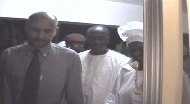 "In this still image taken from a video published last year by Global Witness, Frédéric Cilins, left, appears at a 2006 reception held in Guinea, along side Mamdie Touré, right. Cilins pleaded guilty this year to attempting to pay Touré to destroy evidence ""very, very urgently."""