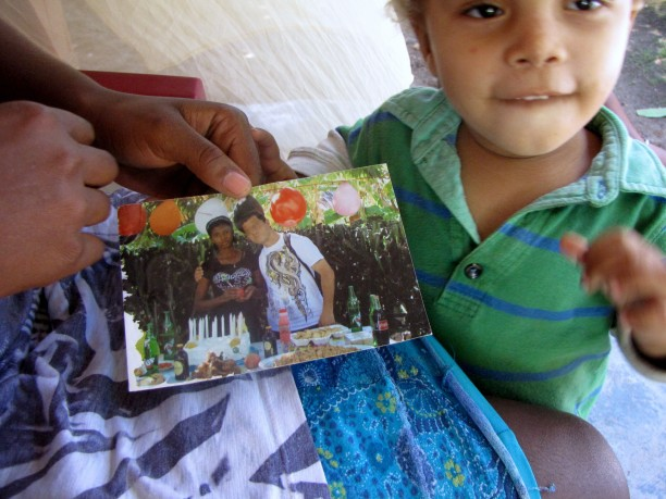 Anderson Joseph, two years old, by a picture of his mother, Rose Mina Joseph, and his alleged father, a UN peacekeeper.