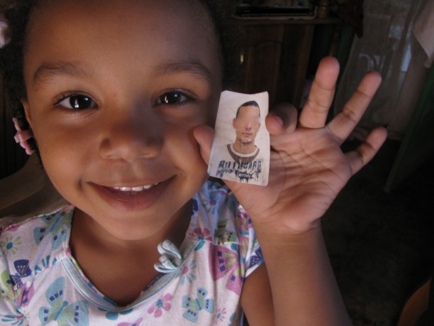 "Sasha Francesca Barrios, 5, holds a picture of the man she calls Papa M, or ""my Dad,"" a former UN peacekeeper from Uruguay ."